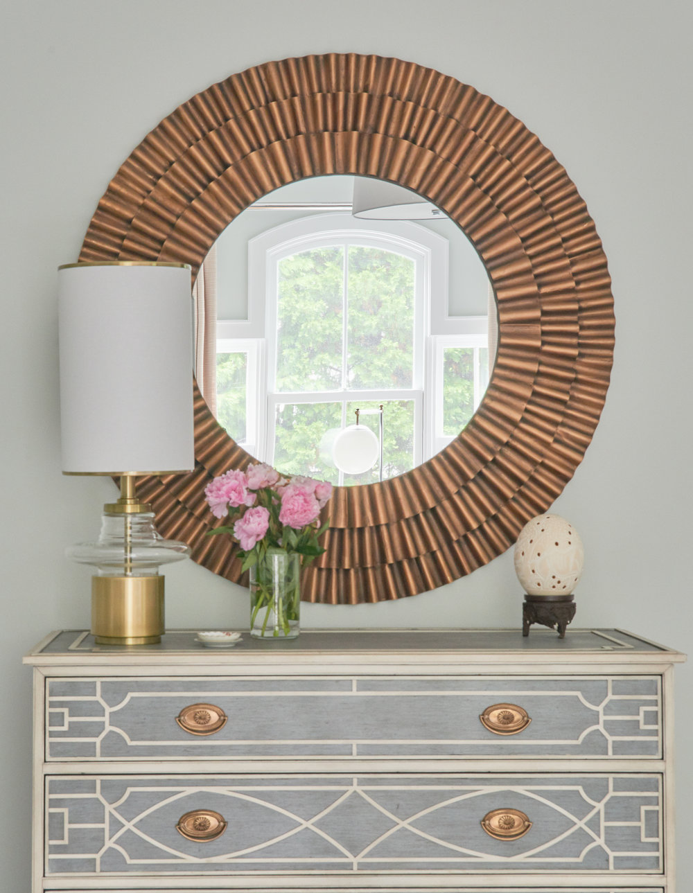 Bedroom dresser with copper drawer pulls and mirror