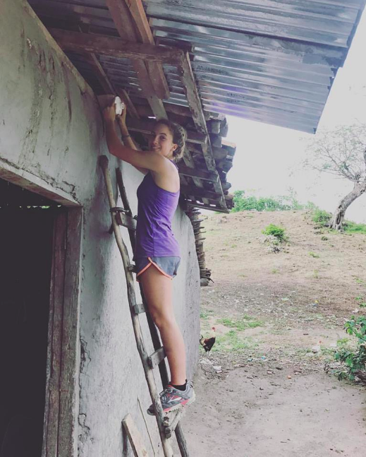 Installing a light bulb on a families Tiny Home in Nicaragua