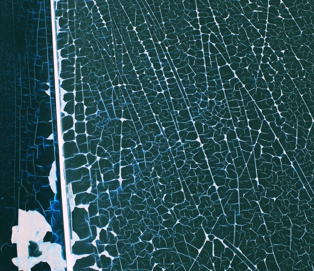 The photograph depicts a frozen body of water. Intricate white cracks contrast the dark turquoise ice. The image is taken from above.