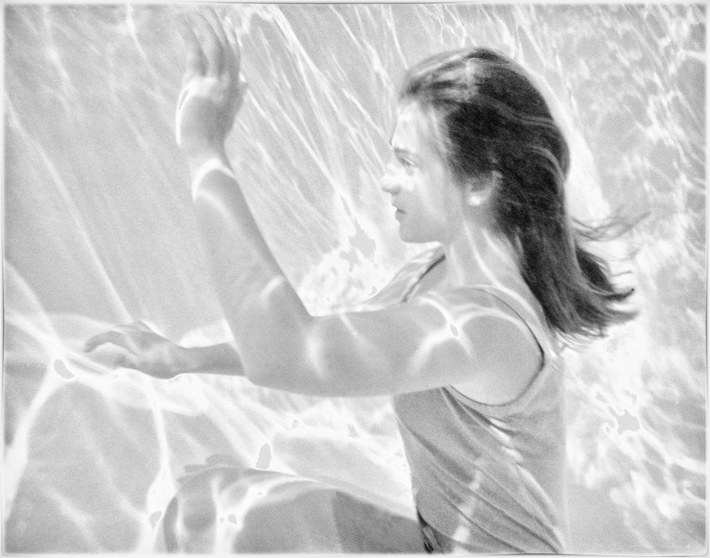 Steve Lautermilch's black and white photograph shows a girl sitting at the bottom of a pool. Her eyes are open, and streaks of light fall across her and over the scene. She holds her left arm up and her right arm straight out in front of her. There is a peaceful but focused expression on her face.
