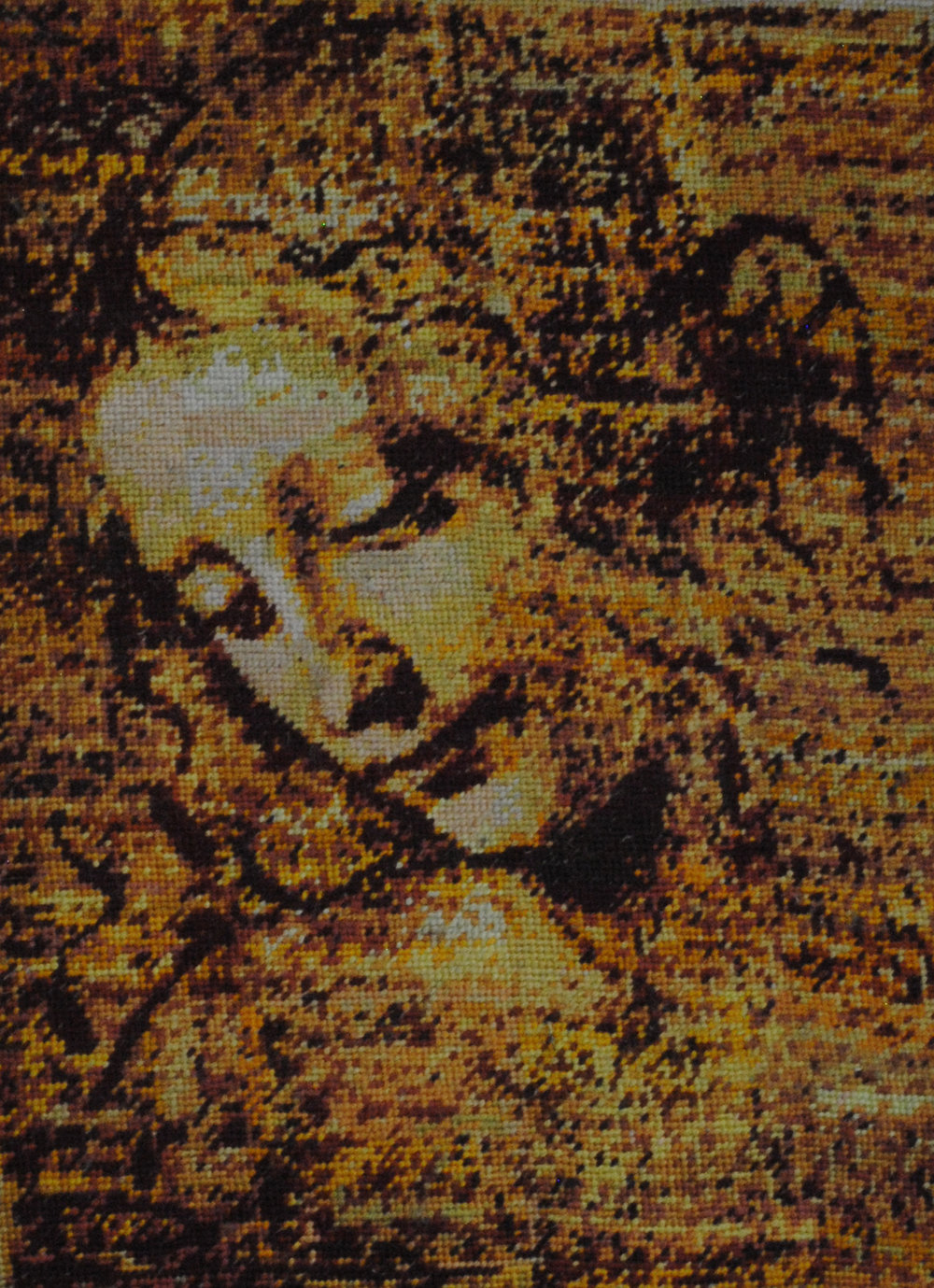 Holly Day's needlepoint is a rendering of one of Leonardo de Vinci's sketches. It shows the head and shoulders of a young woman long, loose hair spread around her, as if blown by wind. The thread is gold, brown, and black. The woman is facing down and seems peaceful, and there appears to be a gentle light on her face.