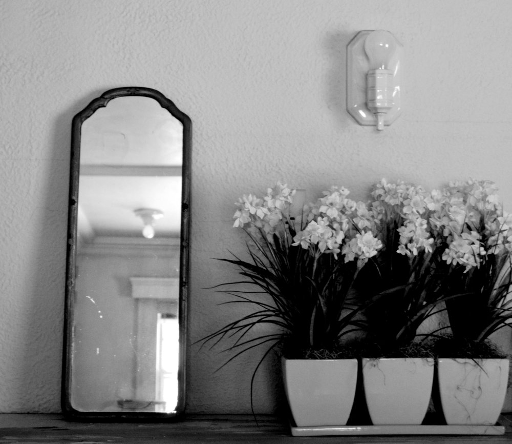 The black and white photograph shows a rectangular mirror with a heavy, wood frame beside three square pots of daffodils.