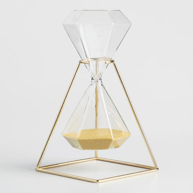 A hexagonal hourglass in a gold base. It is about 25 x 12 x 12 cm. The height of a beer bottle. A lovely decorative piece.