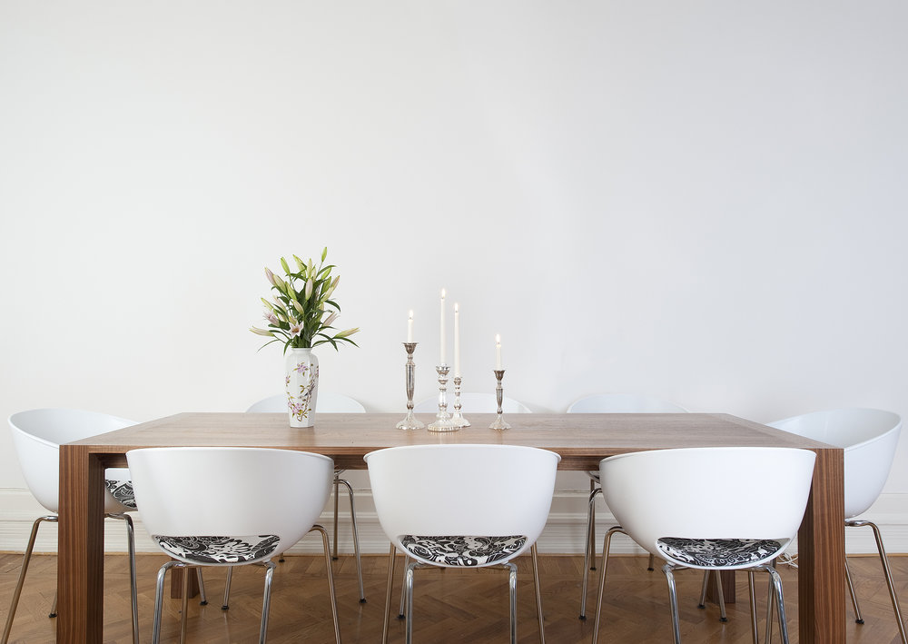 """This dining area needs a large contemporary acrylic or oil on the wall. Any of Bobbie Burgers amazing flower arrangements of canvas would work really well. The size I recommend is 60""""x60"""" or a rectangular piece of 72""""x48"""". The larger the better."""