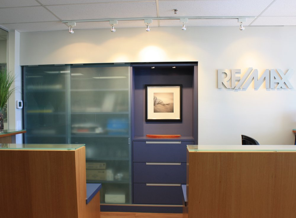 To Execution: Custom Sliding Door System - Reception Area - ReMax Crest Realty (Vancouver BC) - Track is concealed in bulk head and guide is incorporated in millwork. Design: Jessica Eken,  Sophistique Interior Design