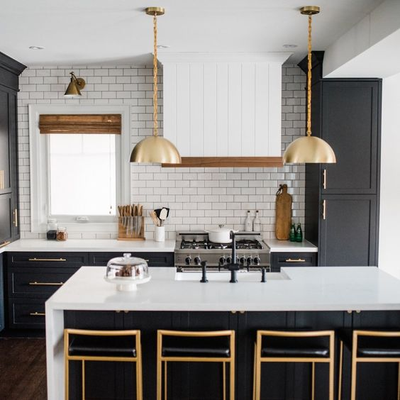 Royce Chain Pendant. Source: Schoolhouse. Rather than small pendants the homeowner choose two larger gold tone ones. This pendant is also gold toned on the inside. The brass barstools pick up on the gold tones. I probably would have chosen a more interesting fabric for the barstools. The, what looks like faux leather in black does not do it for me. This would have been a great opportunity to introduce an interesting floral or geometric fabric design. The white subway tile is perfect and works well with the countertops. The black faucets are great. A brass toned faucet set would work equally well here.