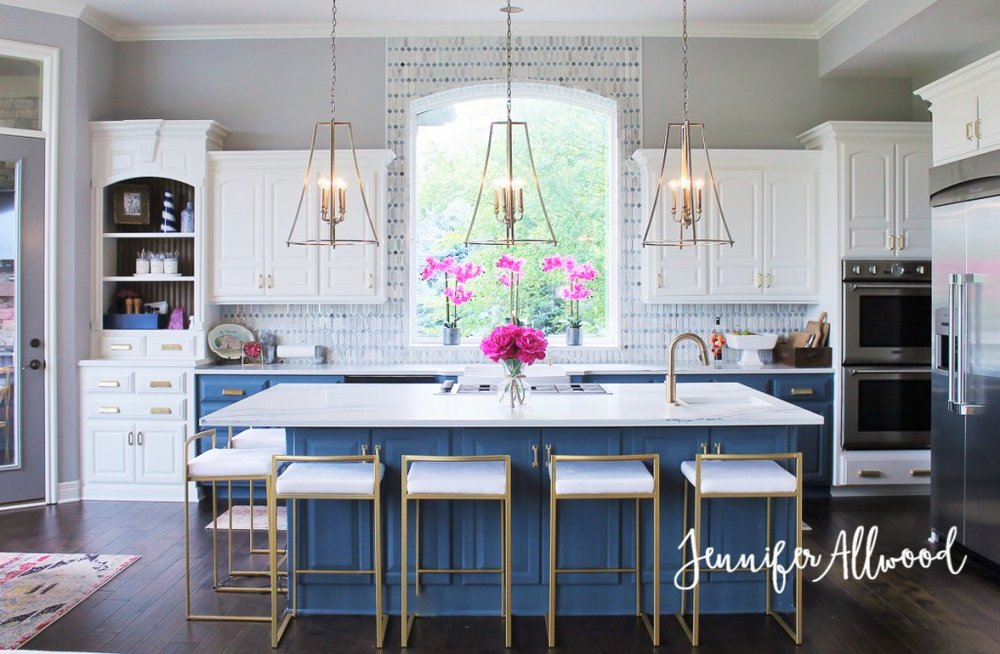 Typical contemporary North American kitchen with lovely brass accents and colour on the base cabinets! Note how the backsplash tile is carried around the arched window giving it emphasis. Design by Jennifer Allowed.