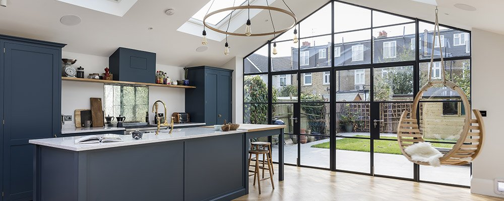 Beautiful kitchen extension with a full wall of contemporary black framed glass windows and doors opening to a small urban garden. Skylights add even further light making the space look large and open. Source: Proficiency Ltd. (UK).