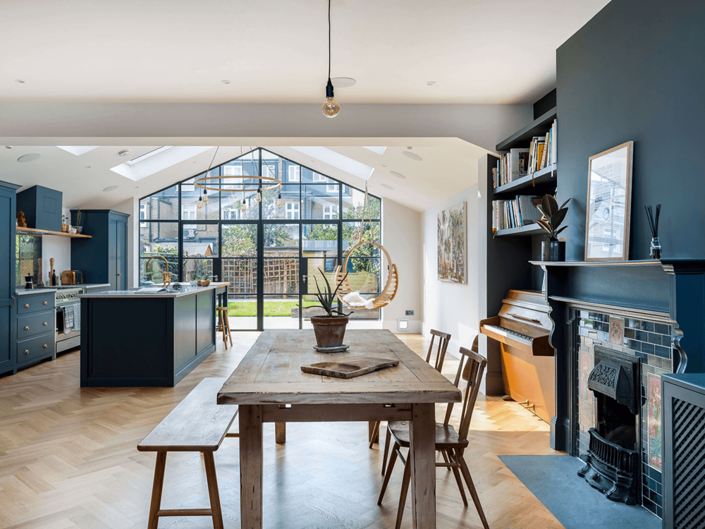 Another image of the Proficiency row house extension. Note how the old fireplace and piano alcove blend seamlessly with the contemporary kitchen and huge bank of windows at the back.
