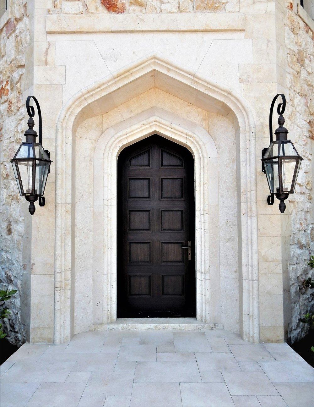 Mediterranean entry door with hand cut stone