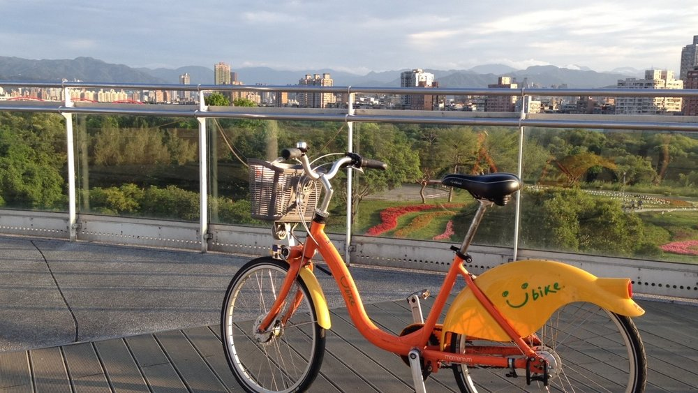 A Youbike parked on a bike overpass next to Tamsui River.