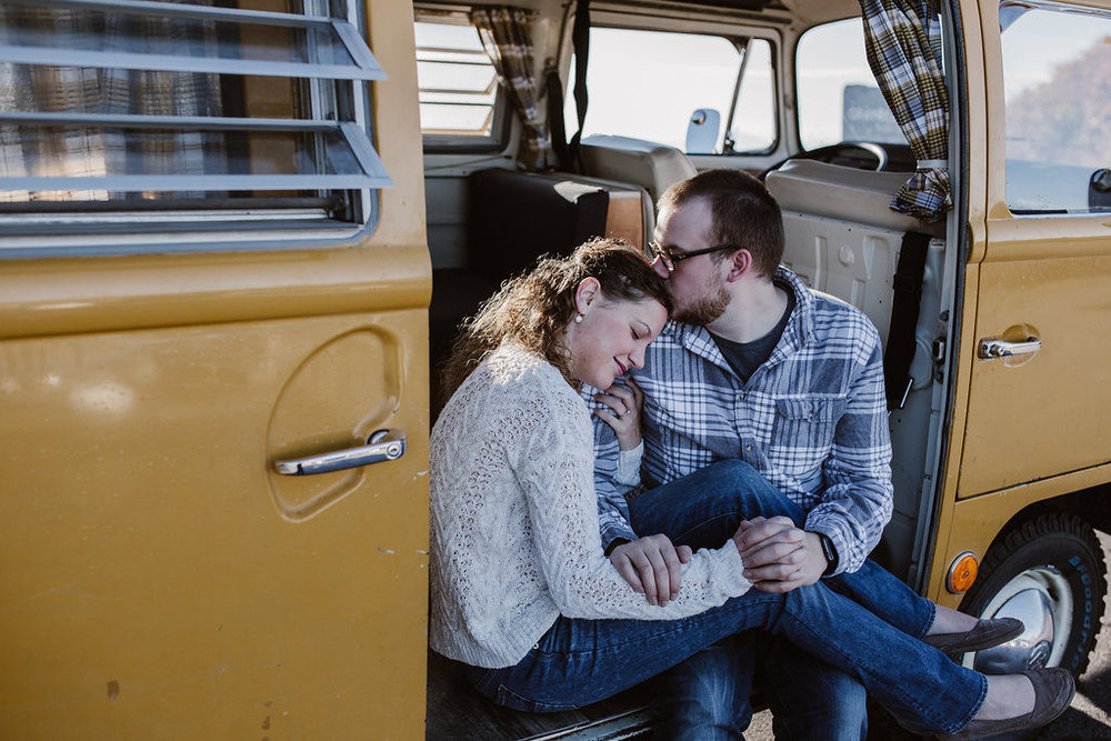 Couple snuggling in yellow, VW bus, engagement session with Tessa Blackstone