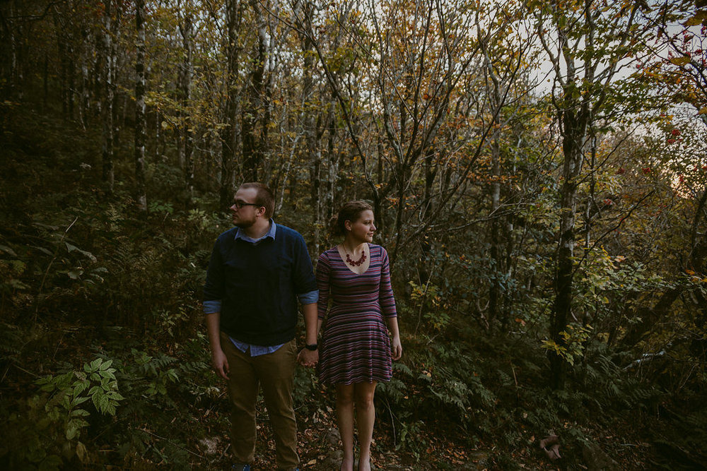 Couple holding hands in woods, engagement session with Tessa Blackstone