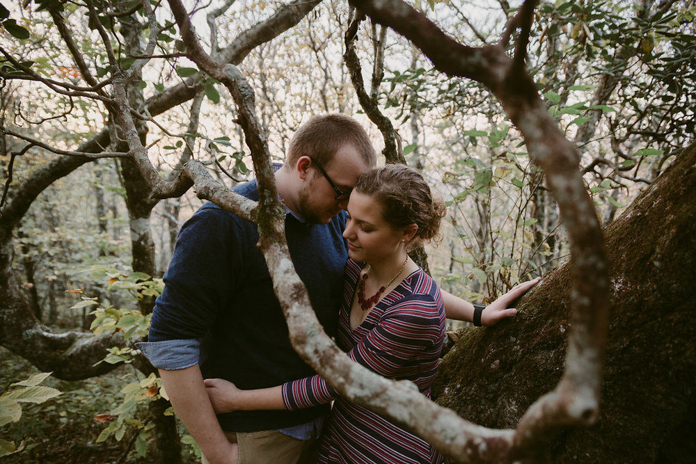 Couple hugging in woods, engagement session with Tessa Blackstone