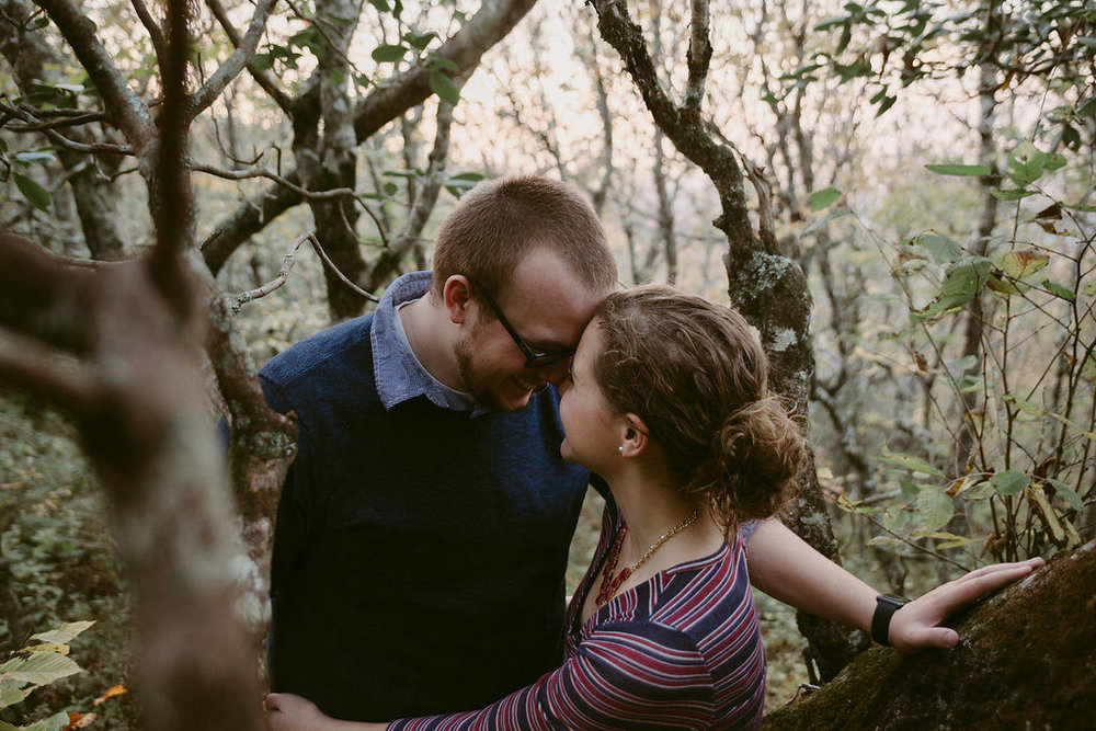 Couple hugging in woodland setting, engagement session with Tessa Blackstone