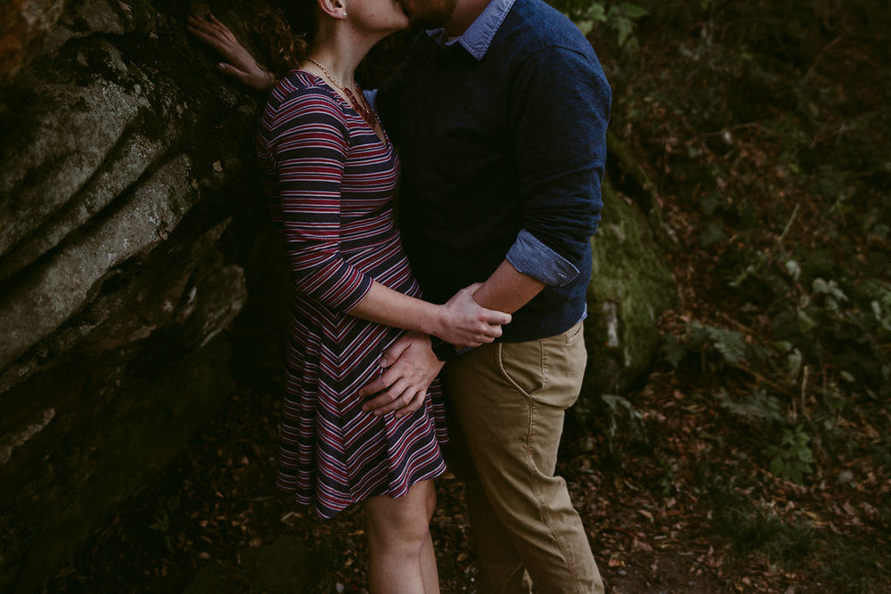 Couple kissing in woodland setting, engagement session with Tessa Blackstone