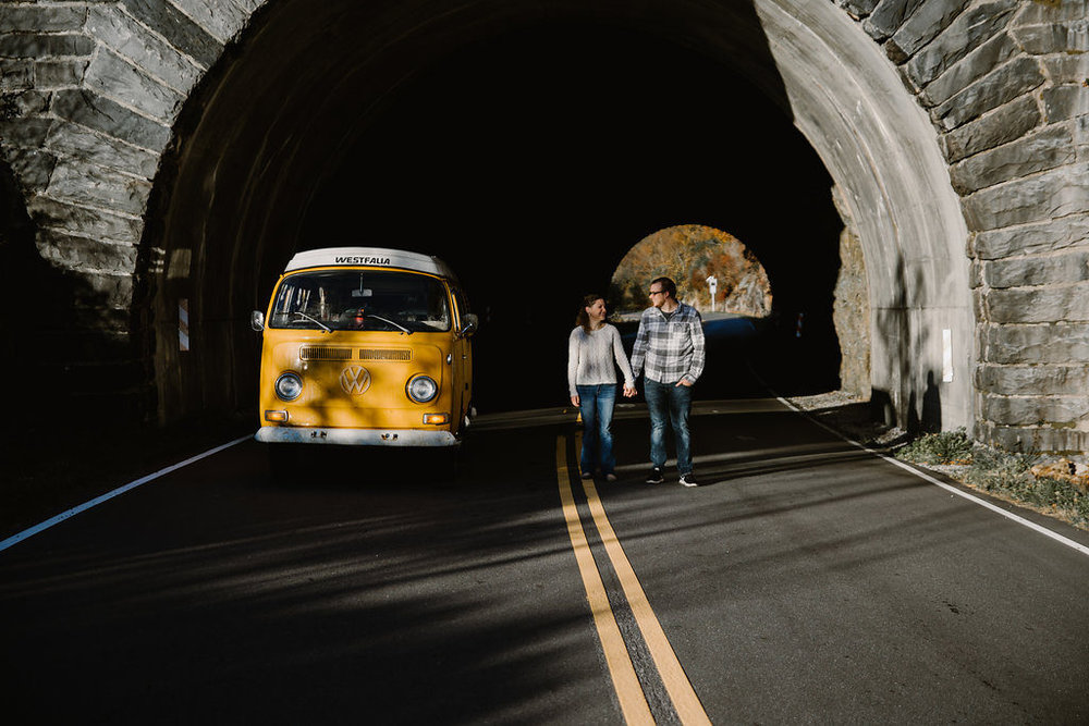 Couple posing in tunnel with yellow VW bus, engagement session with Tessa Blackstone
