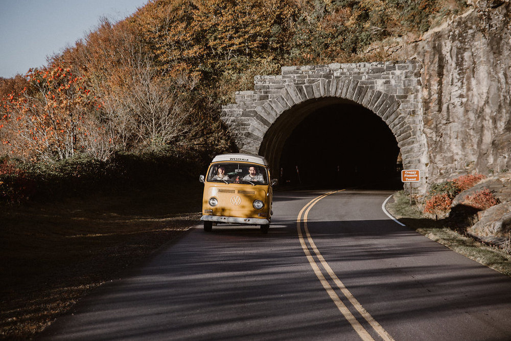 Yellow VW bus driving through tunnel NC, engagement session with Tessa Blackstone