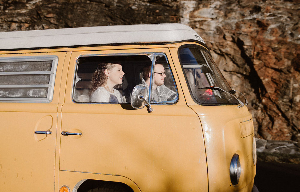 Couple driving in yellow VW bus, engagement session with Tessa Blackstone