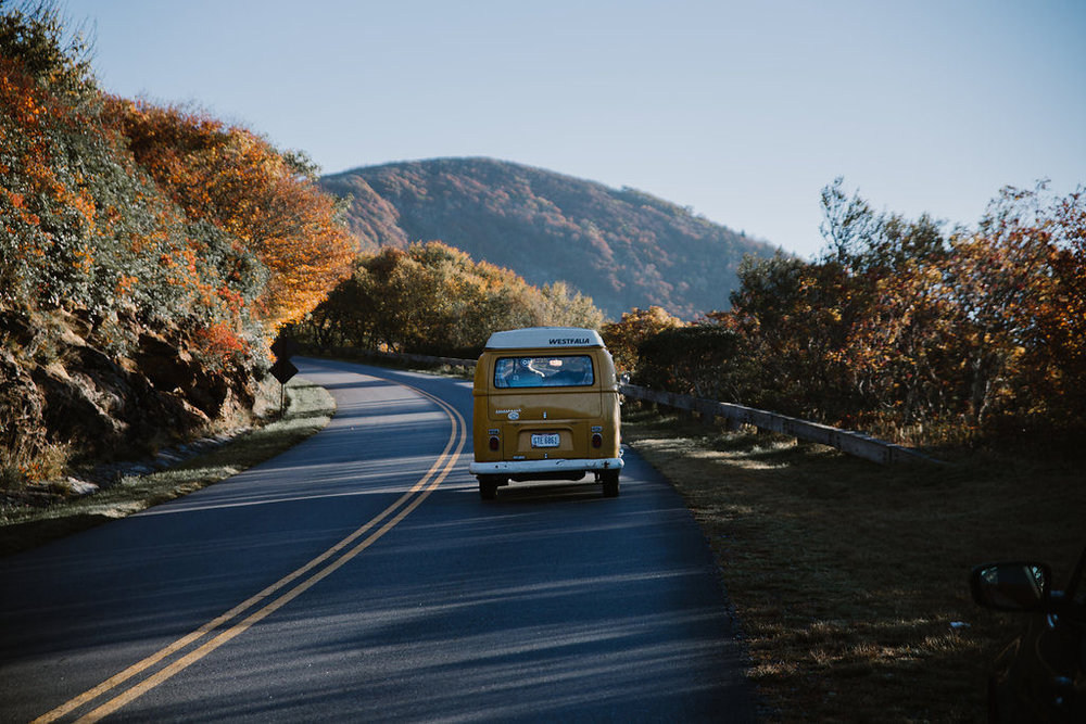 Yellow VW bus driving through NC mountains, engagement session with Tessa Blackstone