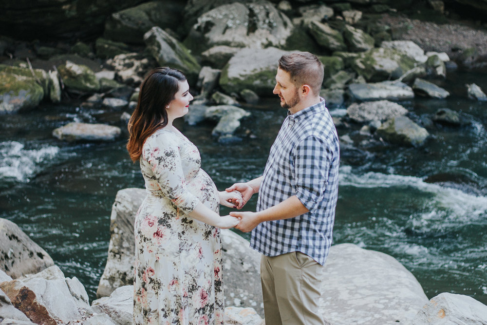 Couple holding hands in front of stream, Artistic + Woodsy Maternity Session | Sarah P Thomas Photography