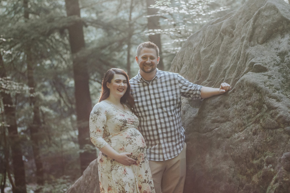 Couple smiling and posing by rock, Artistic + Woodsy Maternity Session | Sarah P Thomas Photography