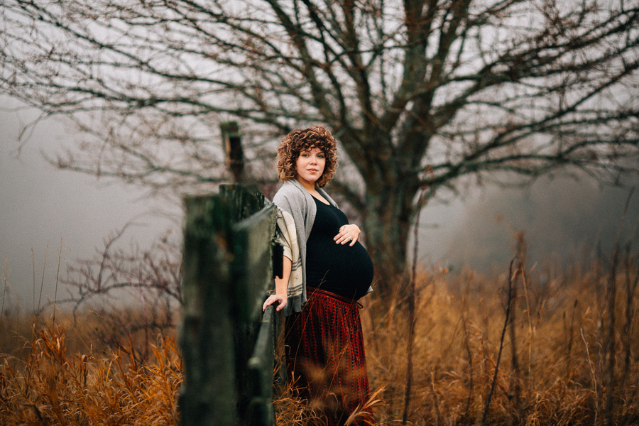 Mom to be by fence in field, Foggy Field Morning Baby Bump Session | Turnquist Photography