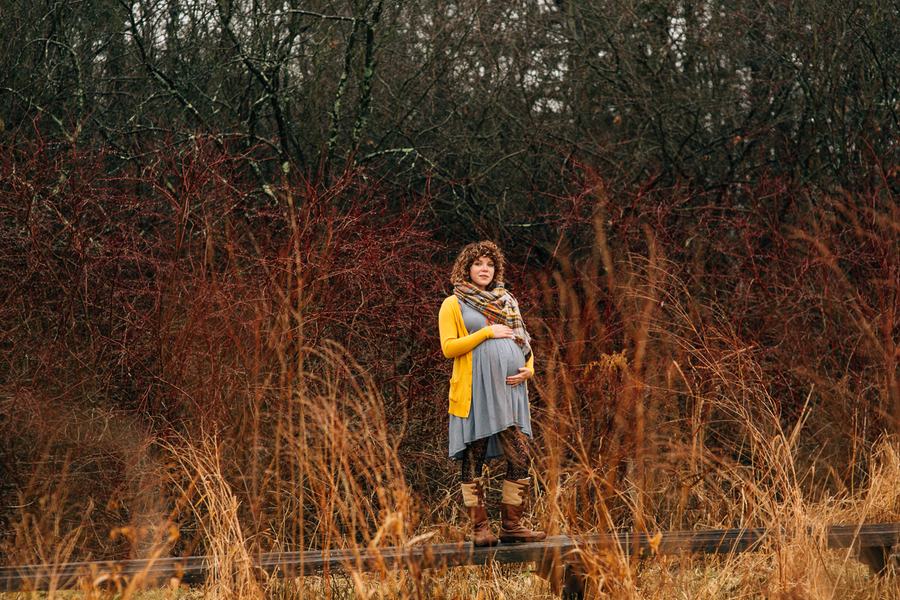 Mom holding belly among red foliage, Foggy Field Morning Baby Bump Session | Turnquist Photography