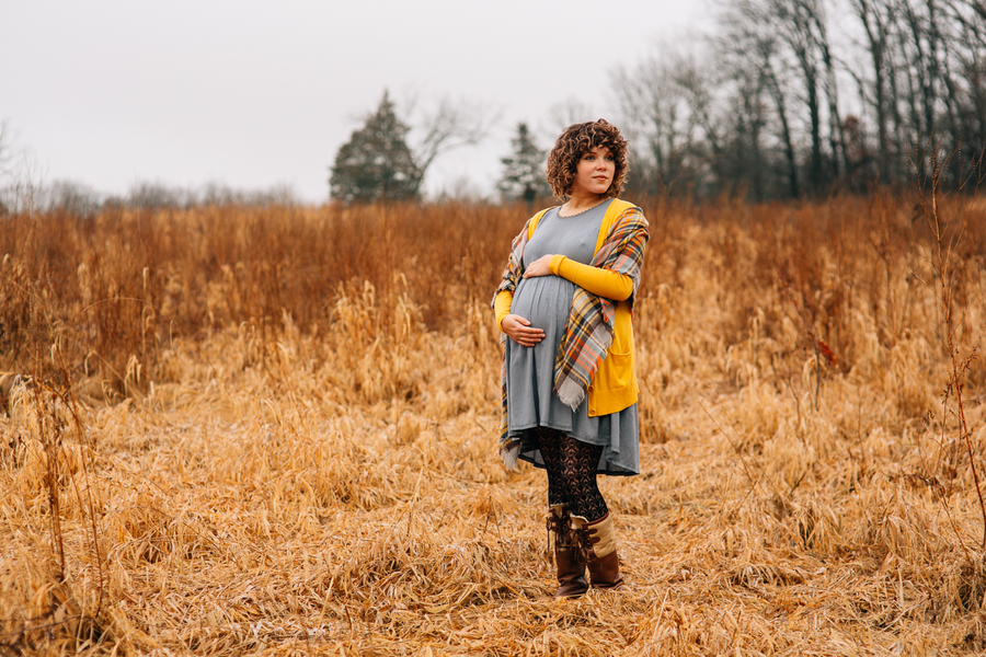Mom to be holding pregnant belly in grassy field, Foggy Field Morning Baby Bump Session | Turnquist Photography