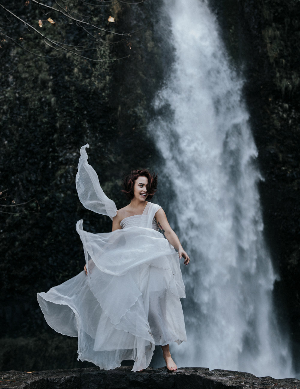 Woman dancing in white dress in front of waterfall, Adventurous Outdoor + Waterfall Couples Session | Croative Photography