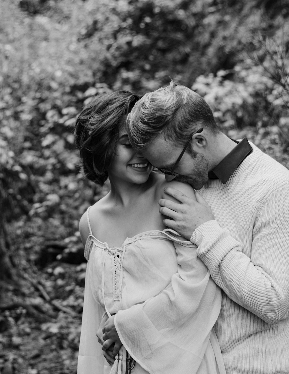 Black and white photo of boyfriend kissing girlfriend's shoulder, Adventurous Outdoor + Waterfall Couples Session | Croative Photography