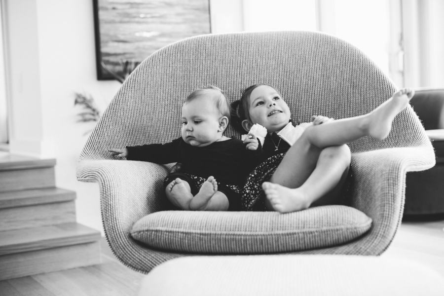 Black and white photo of sisters in chair, Family Lifestyle Session on the Bay | Tiffany Caldwell Photography