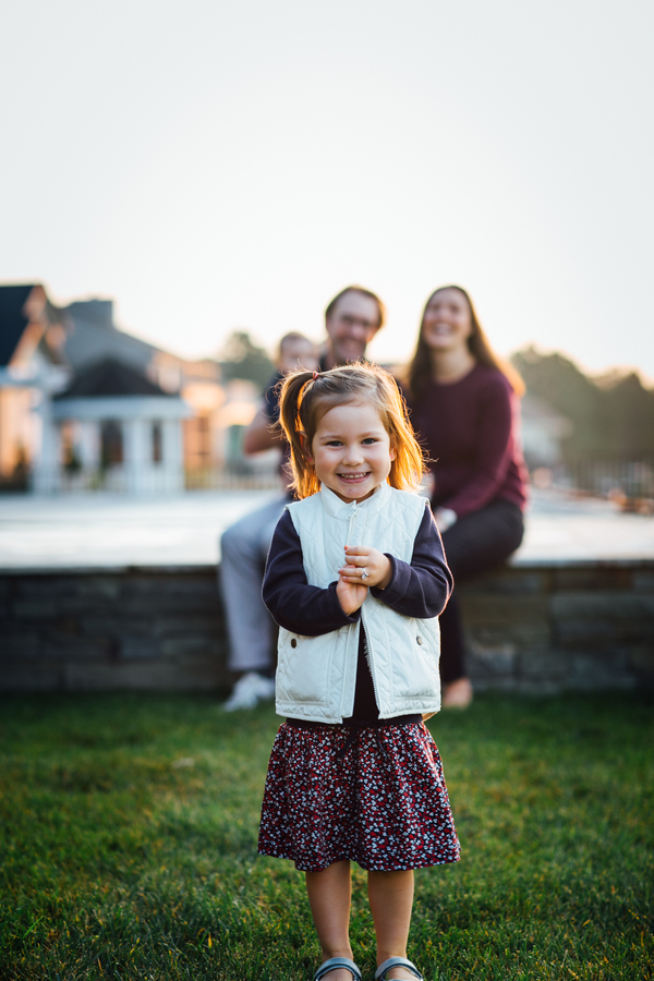 Photo of daughter with family in background, Family Lifestyle Session on the Bay | Tiffany Caldwell Photography