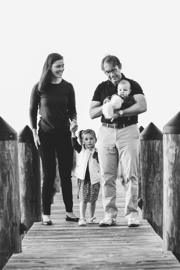 Black and white photo of family walking on pier, Family Lifestyle Session on the Bay | Tiffany Caldwell Photography