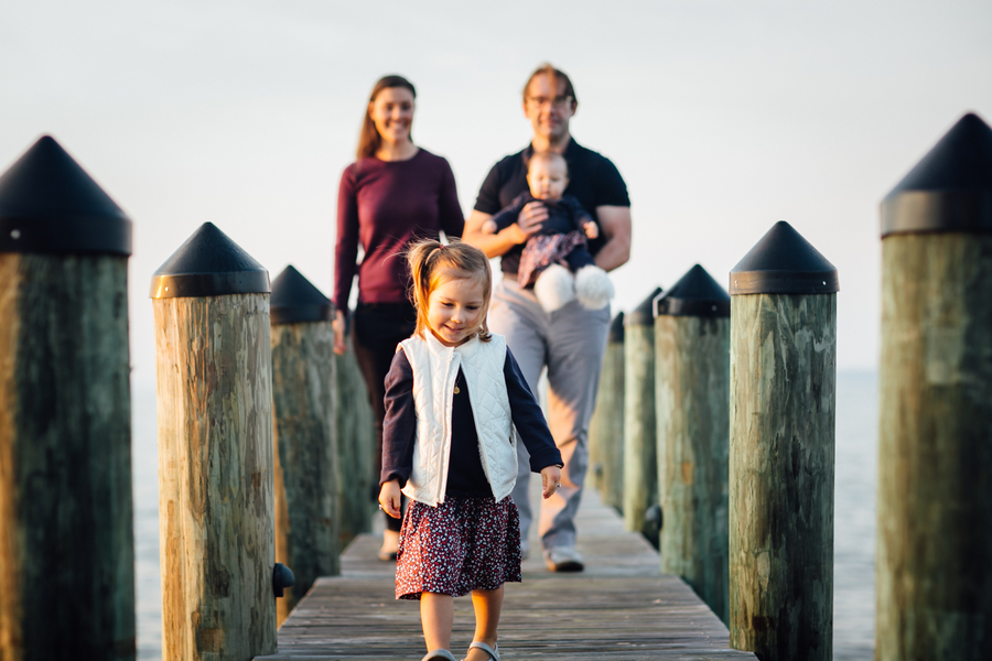 Daughter walking on pier with family in background, Family Lifestyle Session on the Bay | Tiffany Caldwell Photography