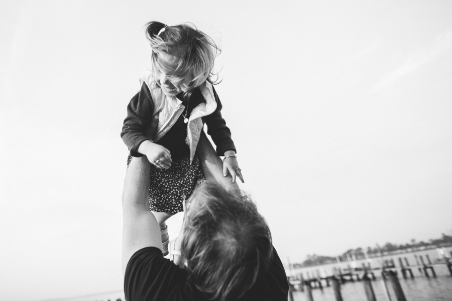 Black and white photo of girl being tossed in air, Family Lifestyle Session on the Bay | Tiffany Caldwell Photography