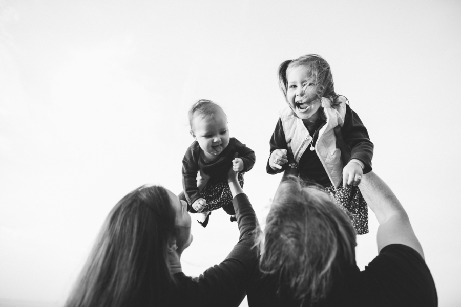Black and white photo of daughters being tossed in air, Family Lifestyle Session on the Bay | Tiffany Caldwell Photography