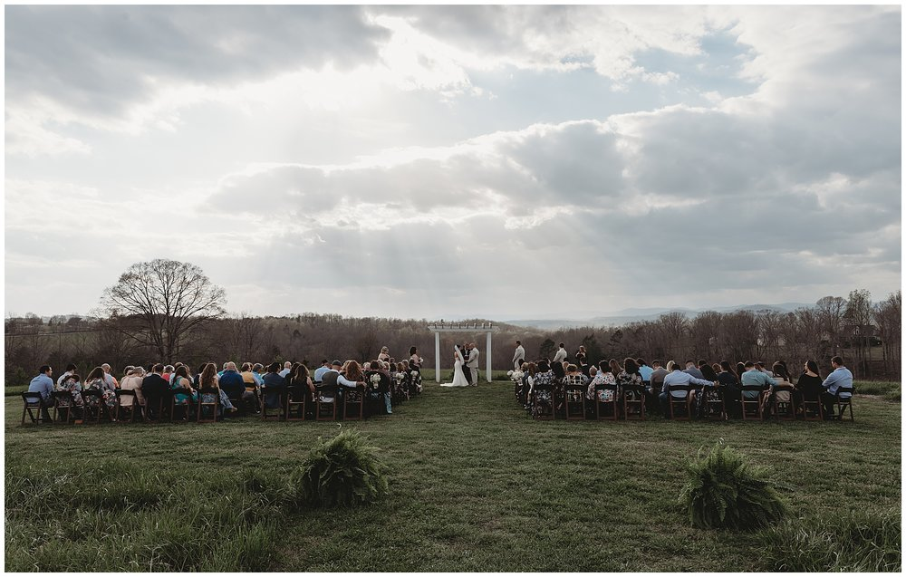 """The sky opened up and cast the most beautiful light on Nicole and Mike during their wedding ceremony. Steven and I gave each other a """"look"""" and quickly changed our camera settings to capture the golden beams of light."""