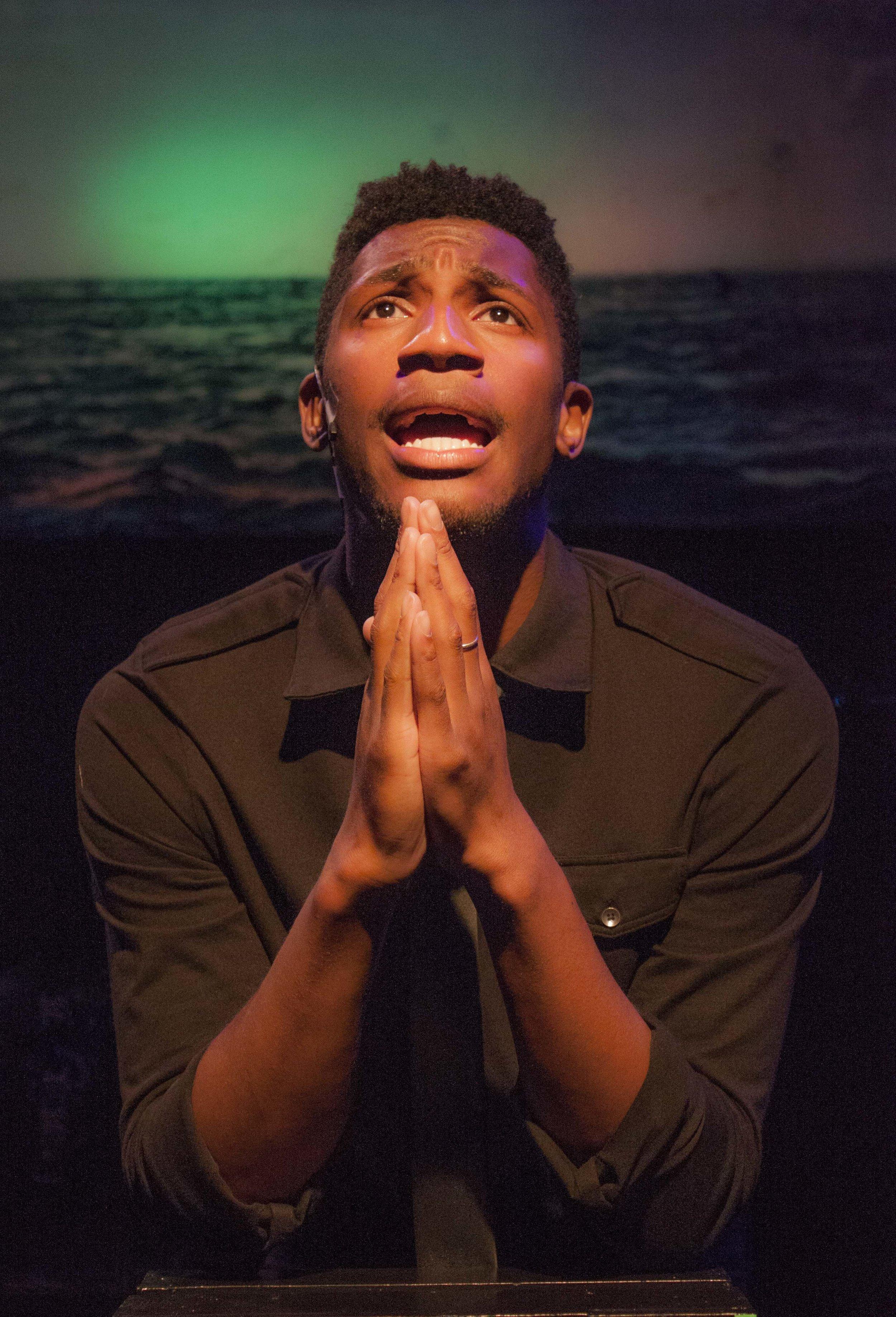 Man 1 (Antonio Tillman) praying through song