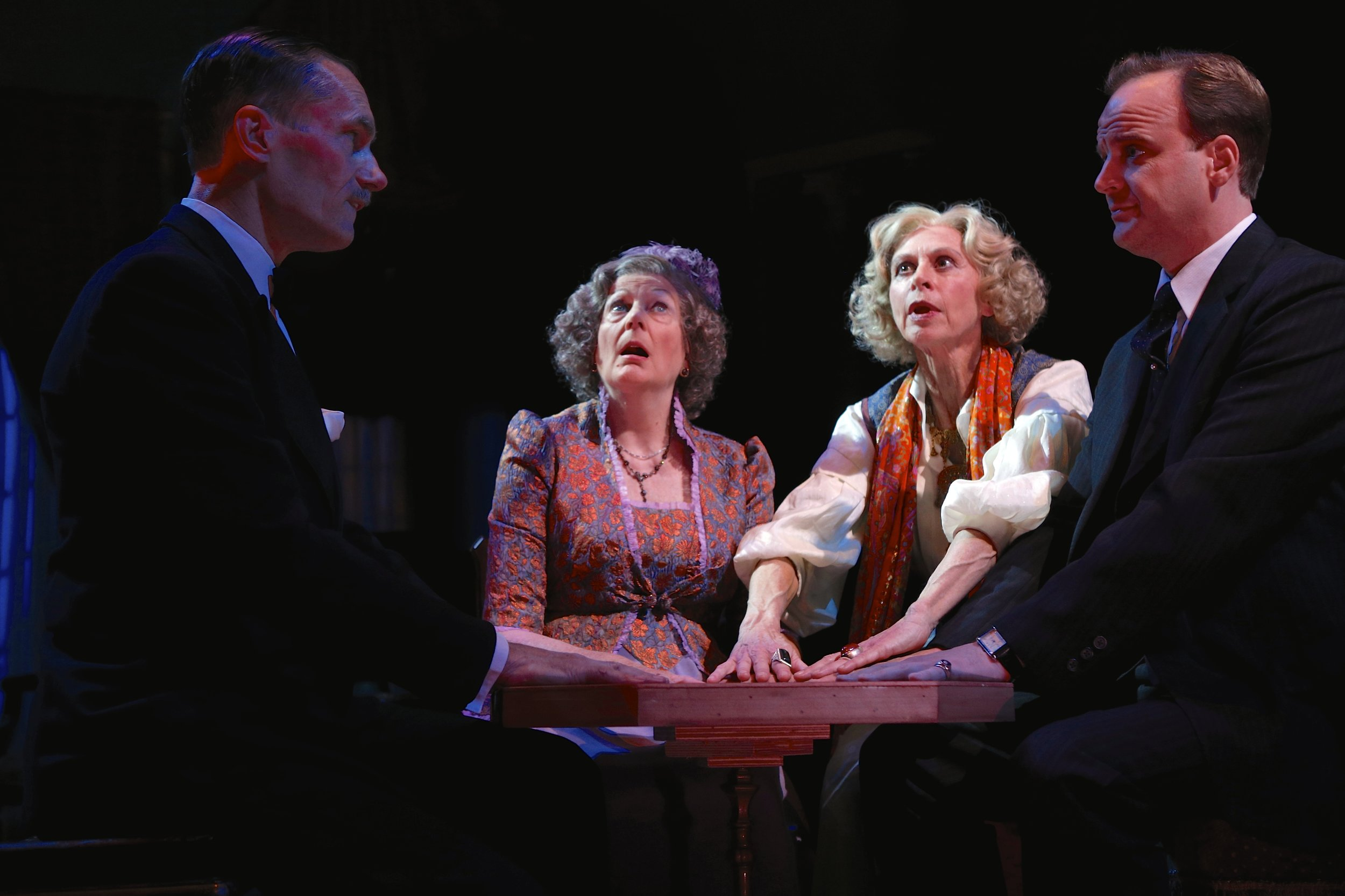 Curzon Dobell (as Dr. Bradman), Elizabeth Ingram (as Mrs. Bradman), Patricia Hodges (as Madame Arcati), and Jeremiah Wiggins (as Charles Condomine) in the Syracuse Stage production of Noel Coward's Blithe Spirit. Photo by: Michael Davis