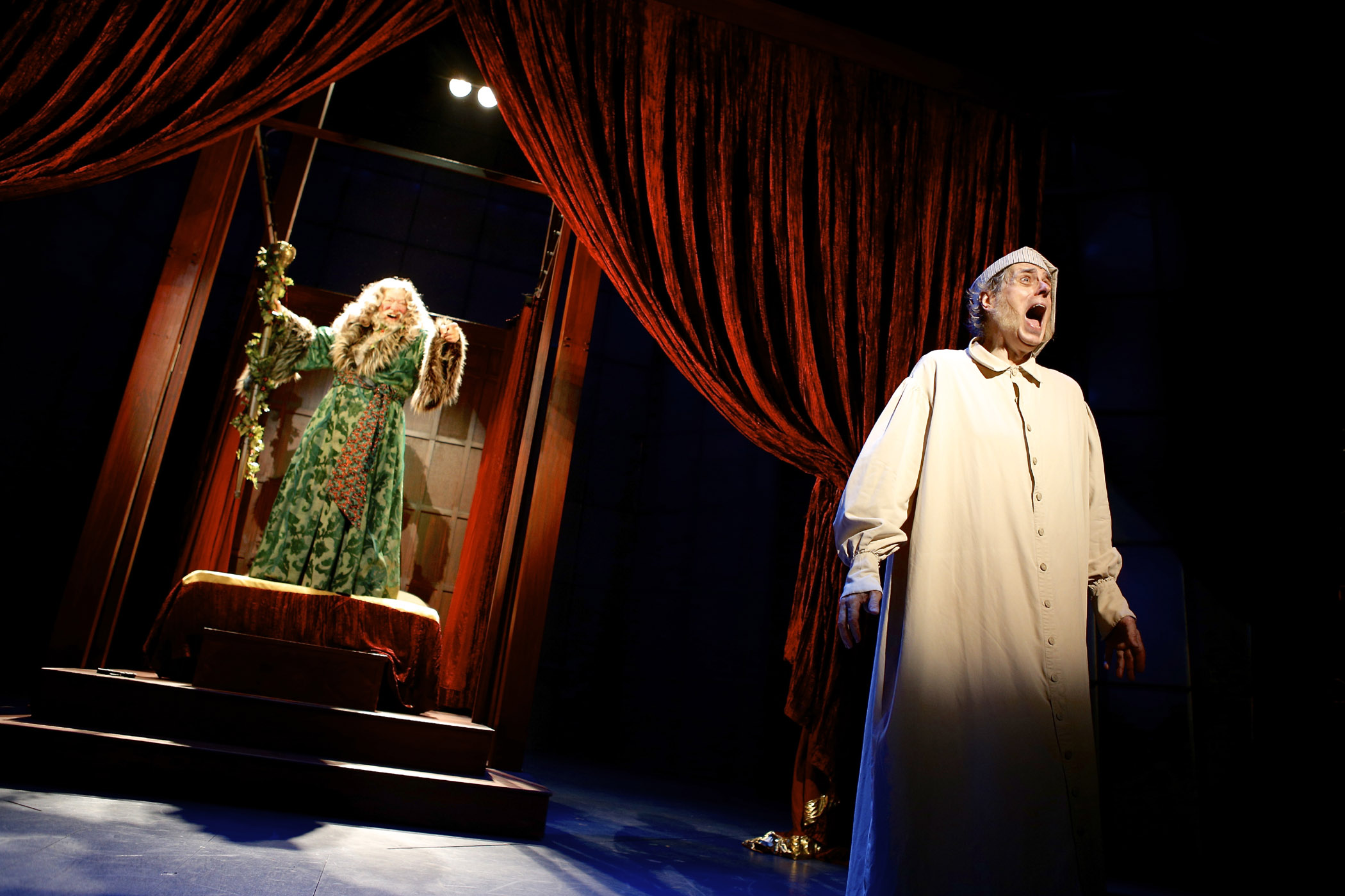 Peter Van Wagner (Ghost of Christmas Present) and Steven Hendrickson (Scrooge) in A Christmas Carol, running through December 29 at Syracuse Stage. Photo by Michael Davis