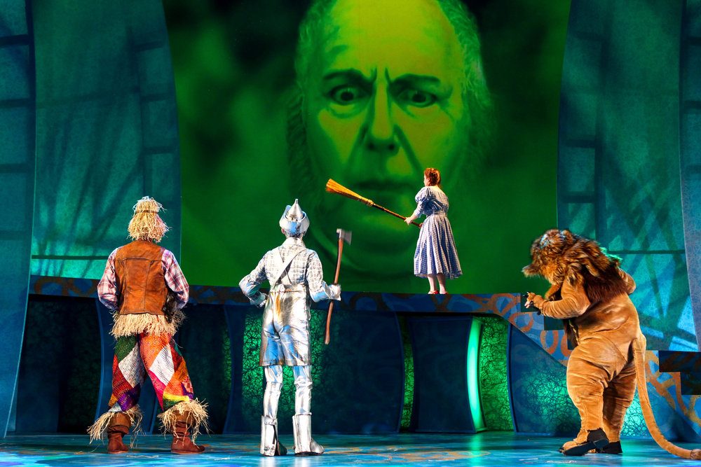 "Crawford Horton, Tucker Breder, David Lowenstein (projection), Kate Jarecki, and Brian Michael Hoffman in Syracuse Stage's production of ""The Wizard of Oz."" Photo by Michael Davis."
