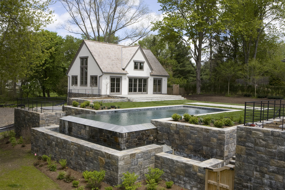 MATERIALS USED: HISPANIA GREY GRANITE POOL SURROUND; CUSTOM GAULT NATURAL VENEER STONE BLEND WALLS: CLAPBOARD HILL BLEND
