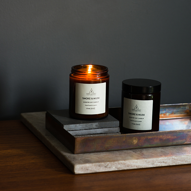 Earl Of East London: Smoke & Musk Candle - A bespoke blend of green balsam fir, alongside wood smoke and deep, musky patchouli. Inspired by the great outdoors, this blend creates a warm & cosy atmosphere that will give you a sense of being in a cabin in the woods.