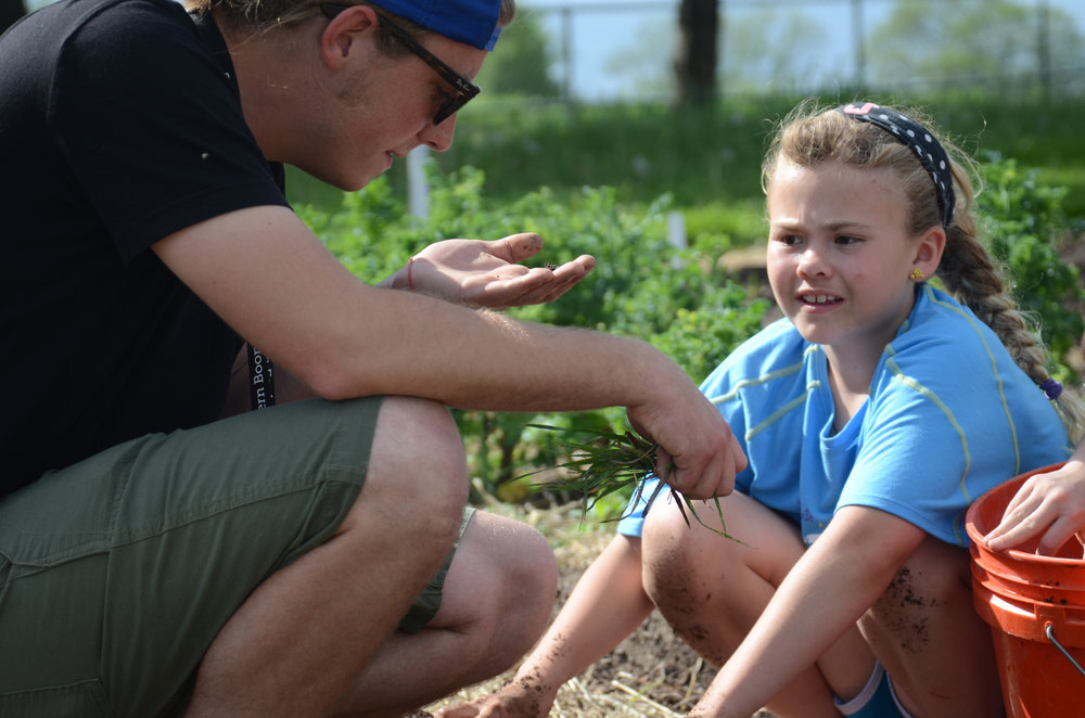 Luke Dietterle, a garden educator at the Southern Boone Learning Garden, examines a bug while weeding with student Jessica Brookeshire in Ashland, Missouri on Wednesday, April 27, 2016. Weeding is one of the chores students can participate in at the garden.