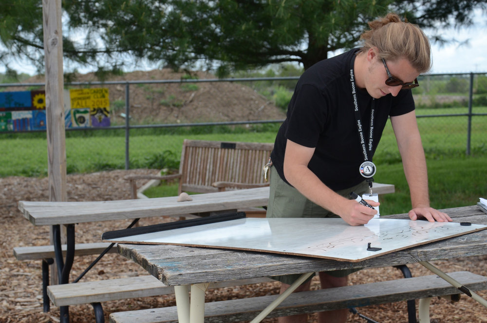 Luke Dietterle, a garden educator at the Southern Boone Learning Garden, writes the day's chores on a white board in Ashland, Missouri on Wednesday, April 27, 2016. Students could choose between weeding, harvesting, mulching and washing dishes.