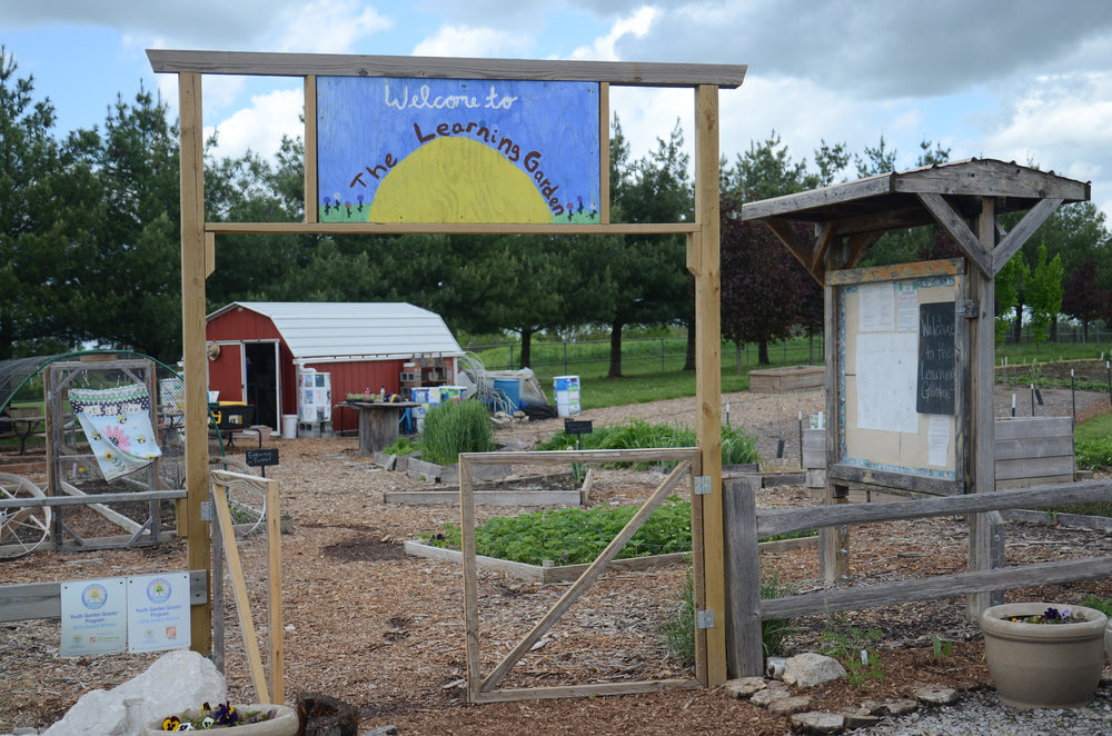 A hand-painted sign stands at the entrance of the Southern Boone Learning Garden on Wednesday, April 27, 2016 in Ashland, Missouri. The garden just barely missed stormy weather that would have canceled activities for the day.