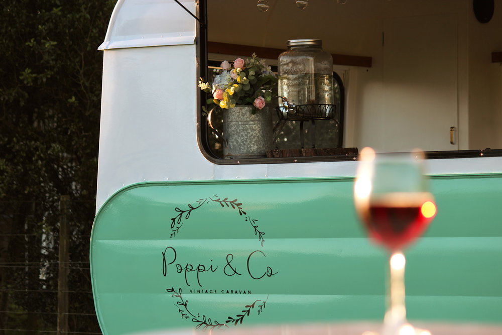 Poppi Vintage Caravan with a glass of wine