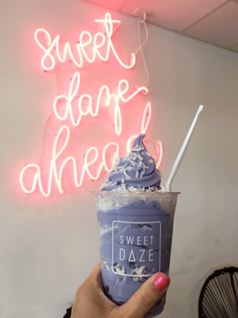 Purple Ube with coconut flakes in a cup.