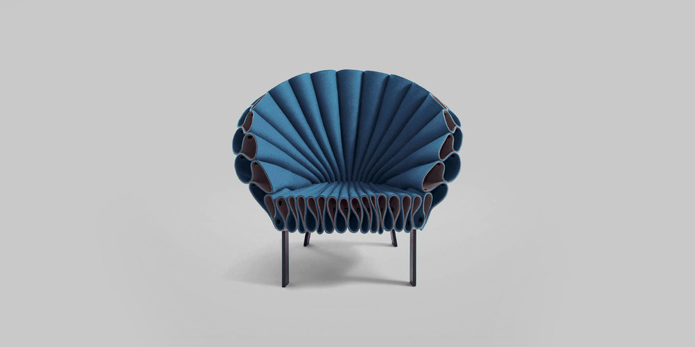 Peacock Chair   Client: Cappellini (Work done at Dror.)   2009  Now a permanent piece in the Metropolitan Museum of Art and an iconic of Cappellini's chair, the Peacock Chair resembles the physical aspects of a peacock and extracts metaphorical substance from its feathers: structured and inviting. Three sheets of felt, a non-woven fabric, are given structure and strength from their peacock like folds creating a comfortable lounge chair, with no sewing or upholstery involved.    Awards: Selected for Metropolitan Museum of Art Permanent Collection 2010
